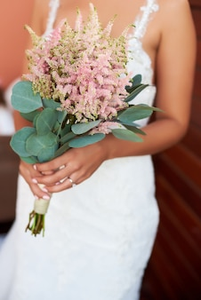 Mariée tenant un bouquet de fleurs dans un style rustique, bouquet de mariée