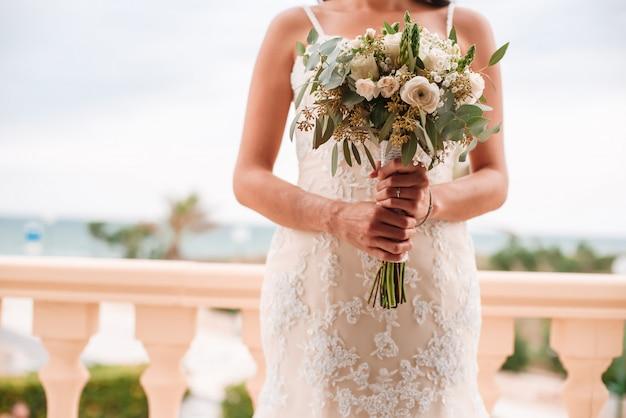 Mariée tenant un bouquet de fleurs dans un style rustique