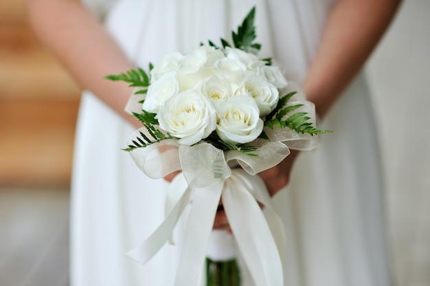 Mariée tenant un bouquet de fleurs de mariage de roses blanches