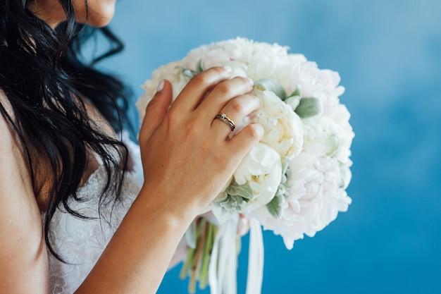 Mariée tenant le bouquet de mariage blanc de roses et fleur d'amour.