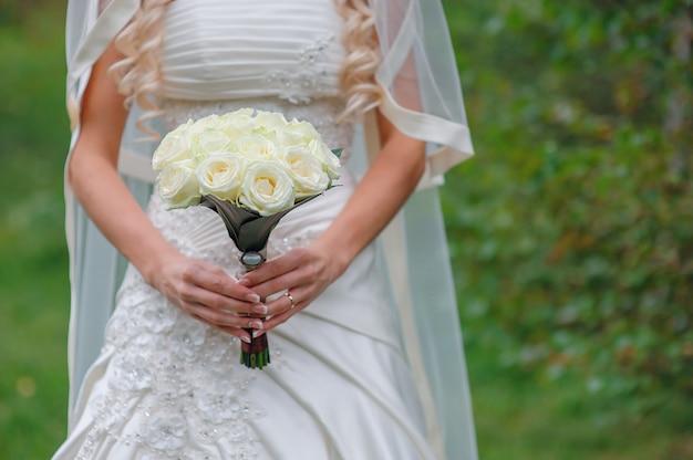 Mariée tenant le bouquet de mariage blanc de roses et fleur d'amour