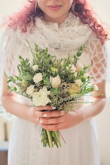 Mariée tenant un bouquet de mariage lumineux avec différentes fleurs