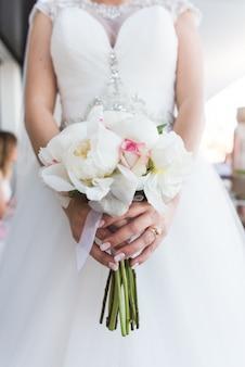 Mariée tenant un bouquet de pivoines blanches et de roses.