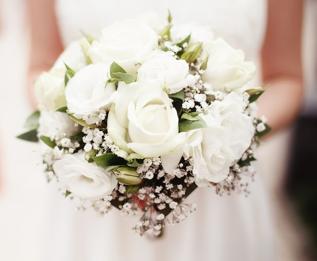 Mariée tenant le bouquet de roses blanches à l'extérieur