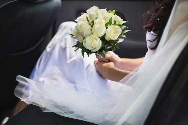 La mariée tenant un bouquet de roses blanches, la mariée assise dans la voiture