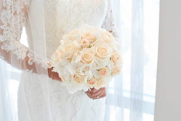 Mariée tenant un bouquet de roses blanches
