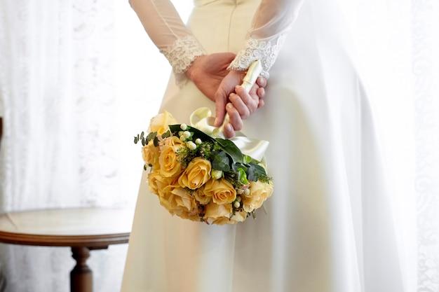 Mariée tenant un bouquet de roses jaunes