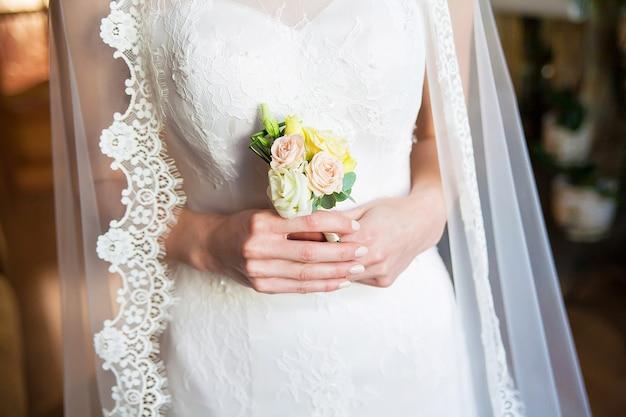 Mariée tenant la boutonnière de mariage dans les mains