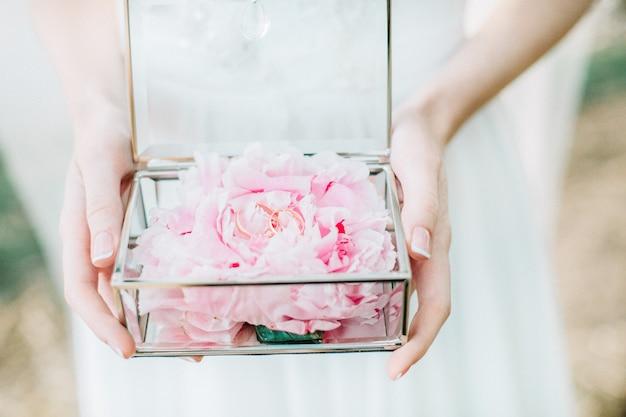 Mariée tenant un cercueil en verre avec des boutons de fleurs de pivoine et des anneaux de mariage. mode nuptiale.