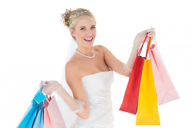 Mariée tenant des sacs à provisions sur fond blanc