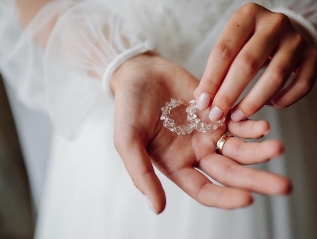Mariée, tenue, boucles d'oreilles, sur, elle, mains