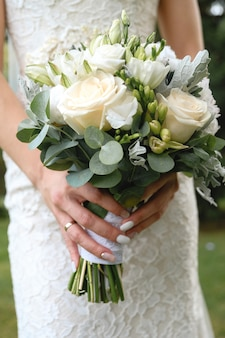 La mariée tient un beau bouquet de mariage blanc. fermer.