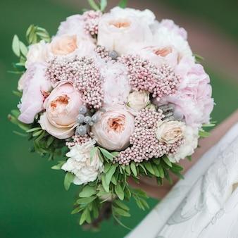 La mariée tient un beau bouquet de mariage de pivoines