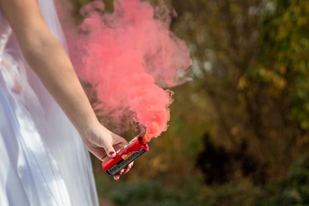 La mariée tient une bombe fumigène dans ses mains, le concept de relations familiales