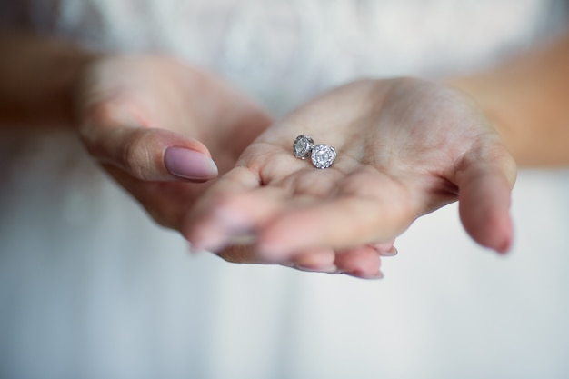 La mariée tient des boucles d'oreilles en argent dans ses bras