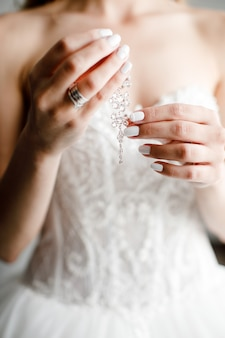 La mariée tient des boucles d'oreilles