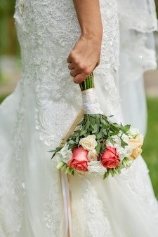 La mariée tient un bouquet de belles fleurs