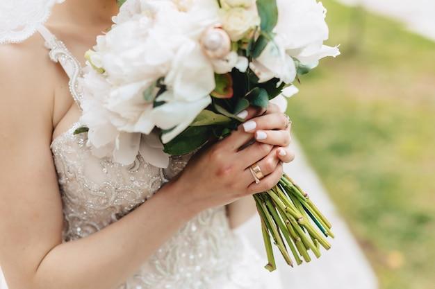 La mariée tient un bouquet de mariage dans ses mains