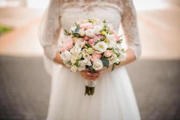 La mariée tient un bouquet de mariage tendre dans ses mains