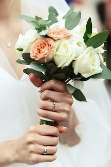 La mariée tient le bouquet de la mariée dans sa main tendre