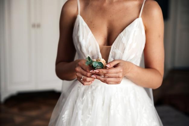 La mariée tient une boutonnière de marié
