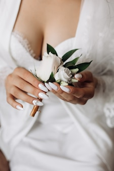 La mariée tient un butonholle