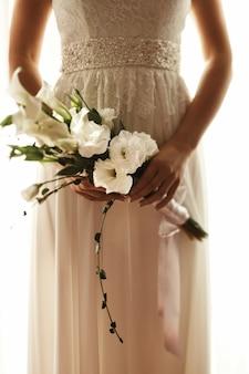 La mariée tient dans ses mains le bouquet de fleurs blanches