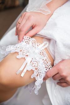 La mariée tient la jarretière de dentelle blanche dans le studio