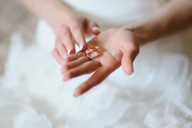 La mariée tient sur la paume deux anneaux d'or