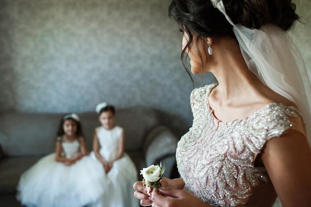 La mariée tient une petite boutonnière blanche dans les bras et regarde les petites filles