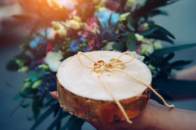 La mariée tient un support en bois avec des anneaux de mariage en or, des anneaux sur un support en bois