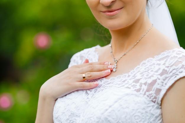 Mariée touchant le pendentif en diamant brillant