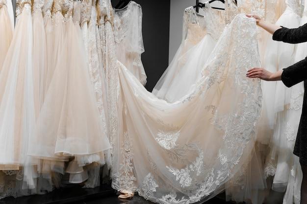 La mariée touche une luxueuse robe de mariée crème blanche sur des cintres.