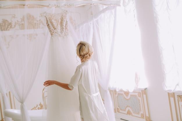 Mariée toucher la robe de mariée de mariage chambre de luxe