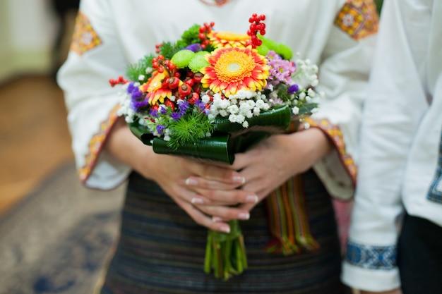 Mariée ukrainienne en broderie native tenant beau bouquet coloré d'automne