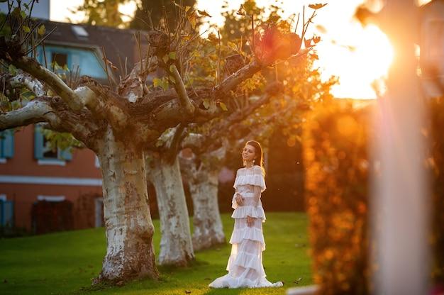 Une mariée vêtue d'une robe de mariée blanche dans un parc d'une ville autrichienne avec de grands arbres au coucher du soleil.