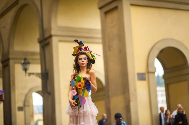 Une mariée vêtue d'une robe de mariée rose avec un bouquet et une décoration inhabituels à gorova à florence, en italie.
