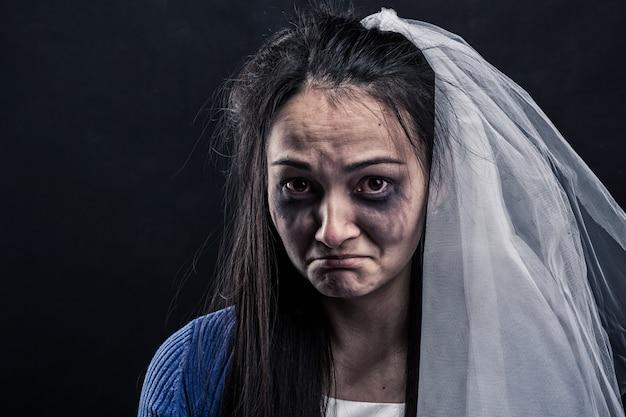 Mariée avec visage taché de larmes sur mur noir