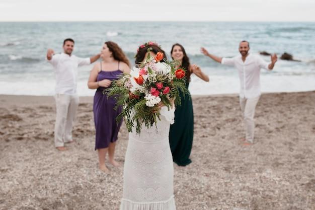 Mariée voulant jeter son bouquet de fleurs