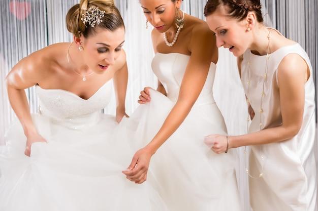 Mariées à la pose de robe de mariée dans la boutique
