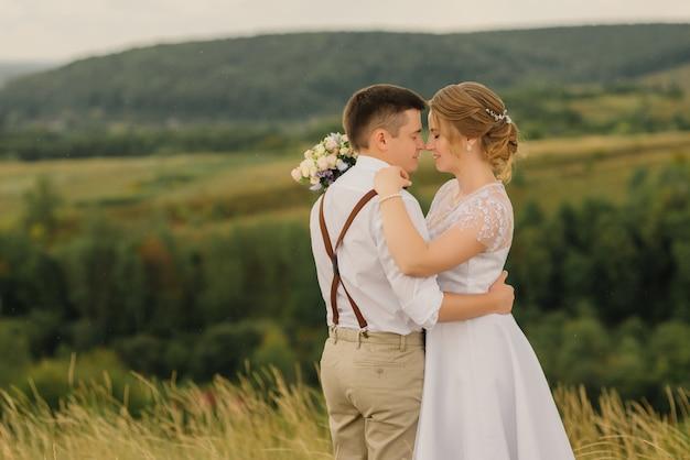 Les mariés amoureux s'embrassent en s'inclinant la tête, contre un paysage magnifique.