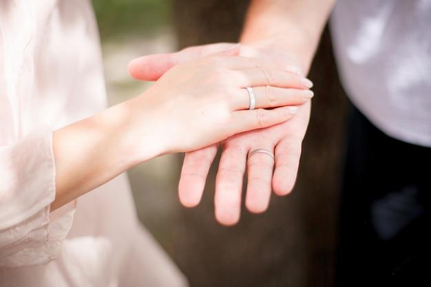 Les mariés avec des anneaux sur leurs annulaires tiennent leurs mains ensemble.
