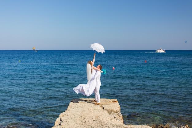 Les mariés au bord de la mer le jour de leur mariage.