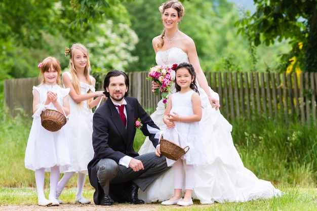 Les mariés au mariage avec les enfants de demoiselle d'honneur