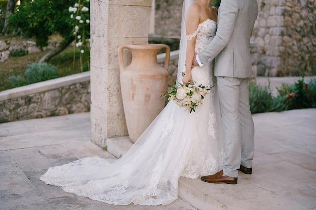 Les mariés avec un bouquet se tiennent près d'une belle arche en pierre