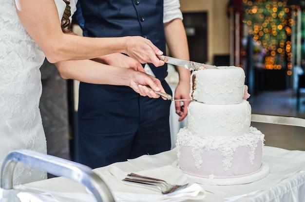 Les mariés coupent le gâteau de mariage traditionnel