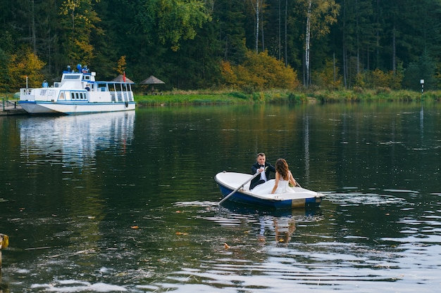 Les mariés dans une barque sur le lac au coucher du soleil