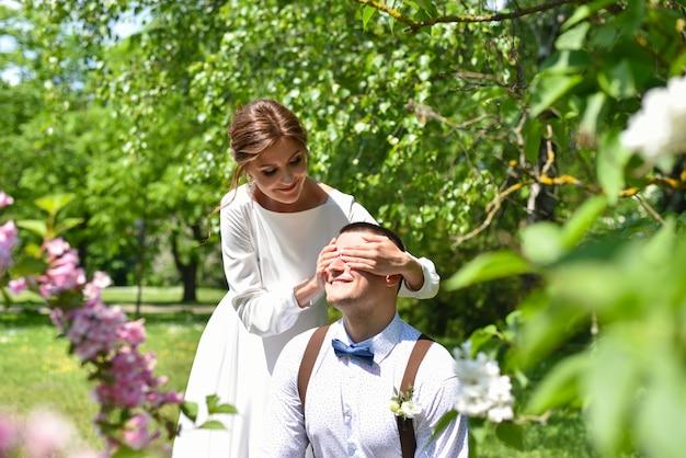 Les mariés dans un bouquet se promènent dans un parc verdoyant