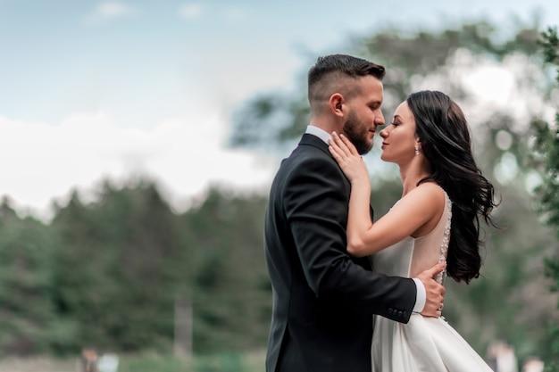 Mariés debout sur le chemin dans le parc