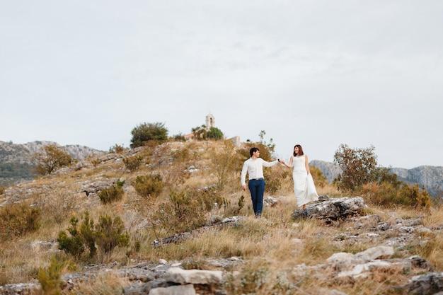 Les mariés descendent de la montagne, le marié tient la main des mariées